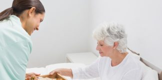 Elderly woman taking a breakfast with home nurse
