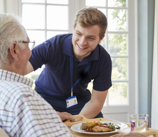 Male care worker serving dinner