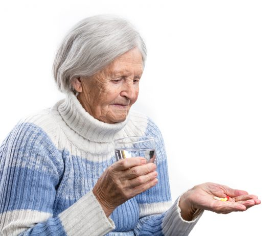 Old lady taking tablet